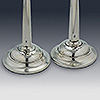 Circular silver candlestick bases with hallmarks to top surfaces