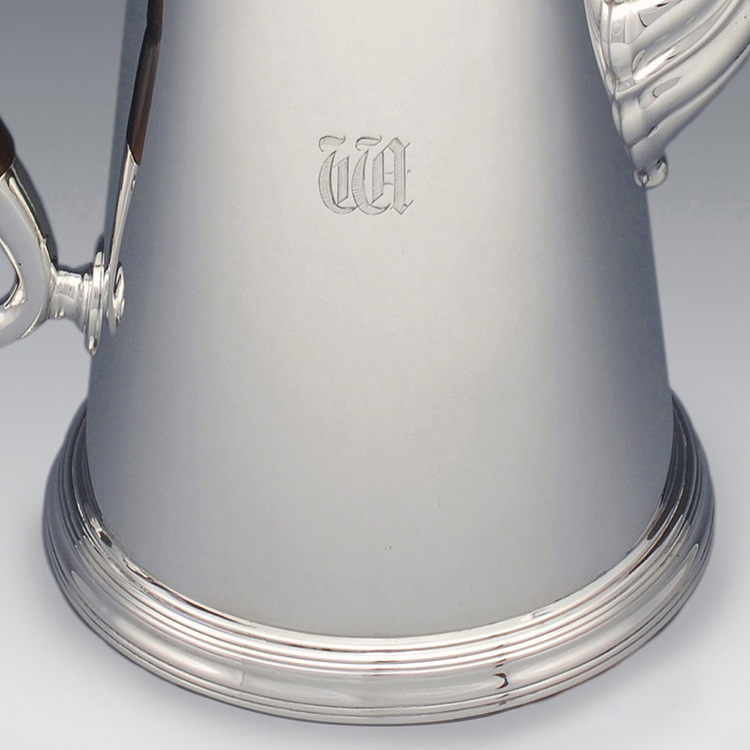 Lower side of coffee pot showing engraved initials TTA